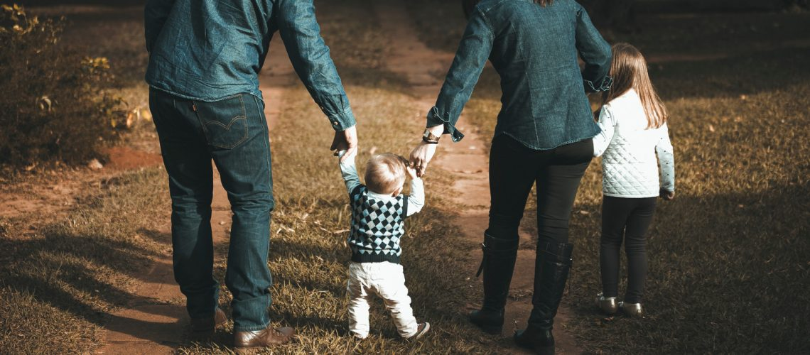 Parents with young son and daughter on a walk