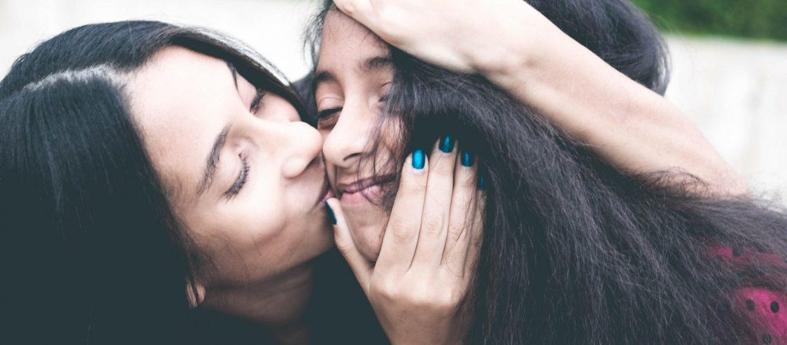 Woman Kissing Cheek of Girl Wearing Red and Black Polka-dot Top